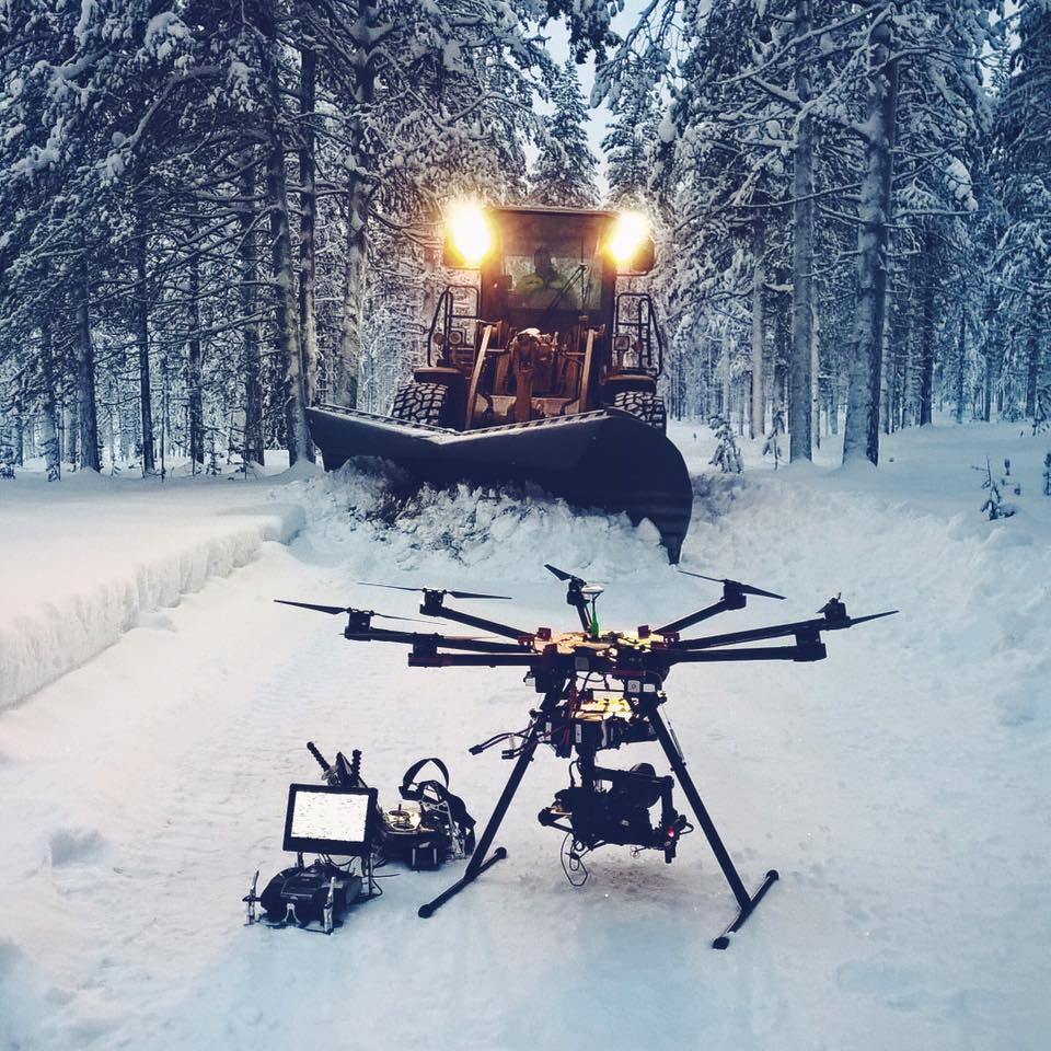 drone sits on snow in front of snowplow in Lapland