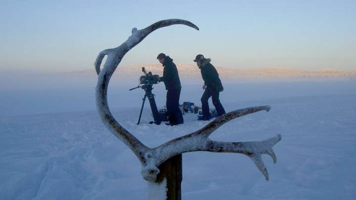 Filmmakers and gear in the snow, framed with reindeer antlers