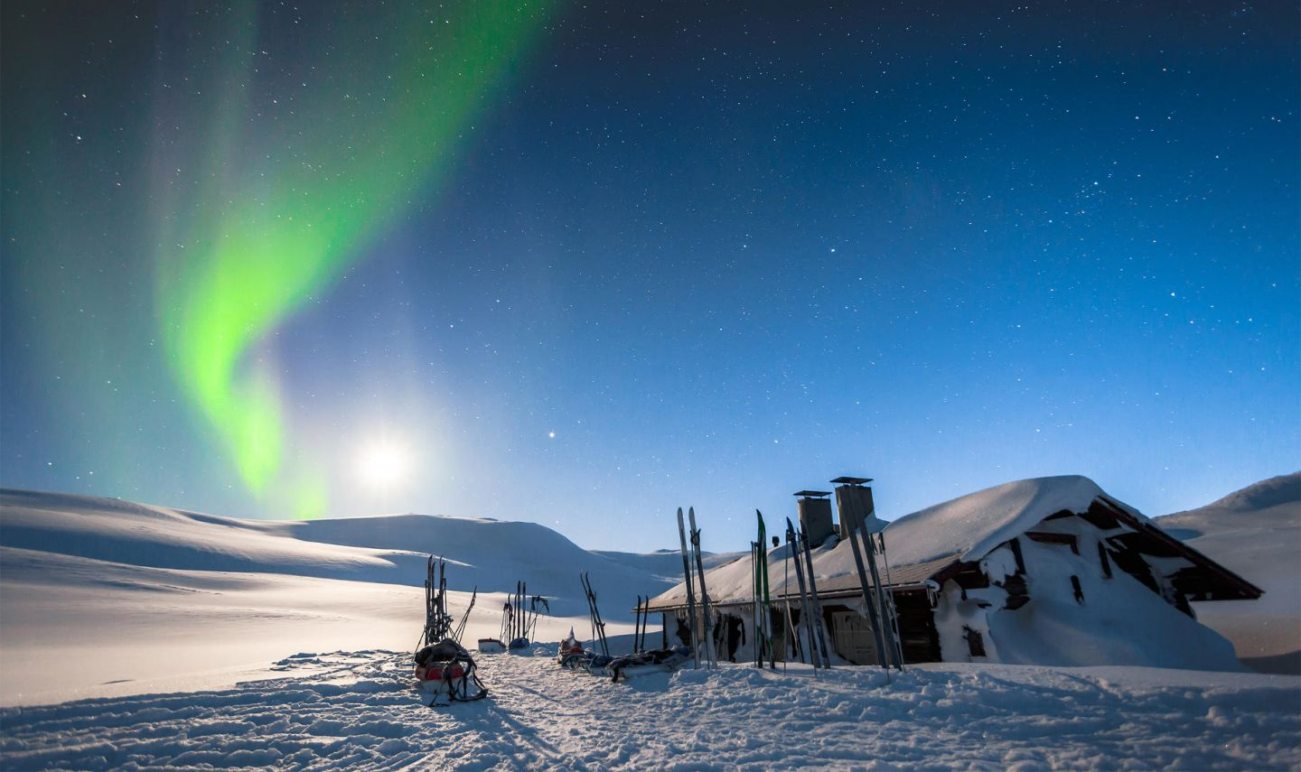 auroras over a snowy cabin in Lapland