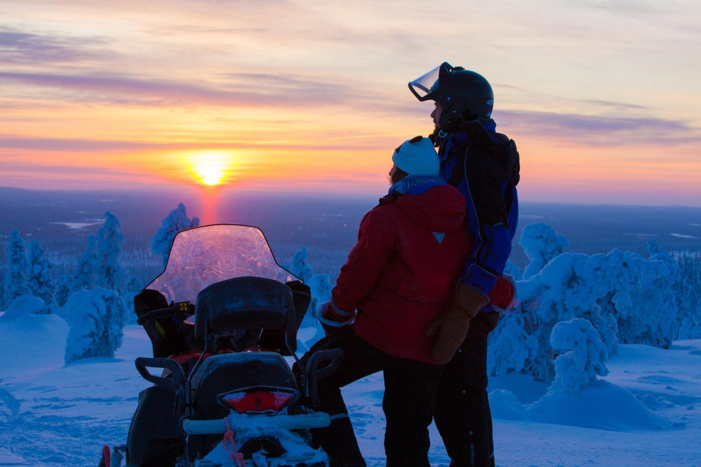 snowmobile ride at sunset during winter in Lapland