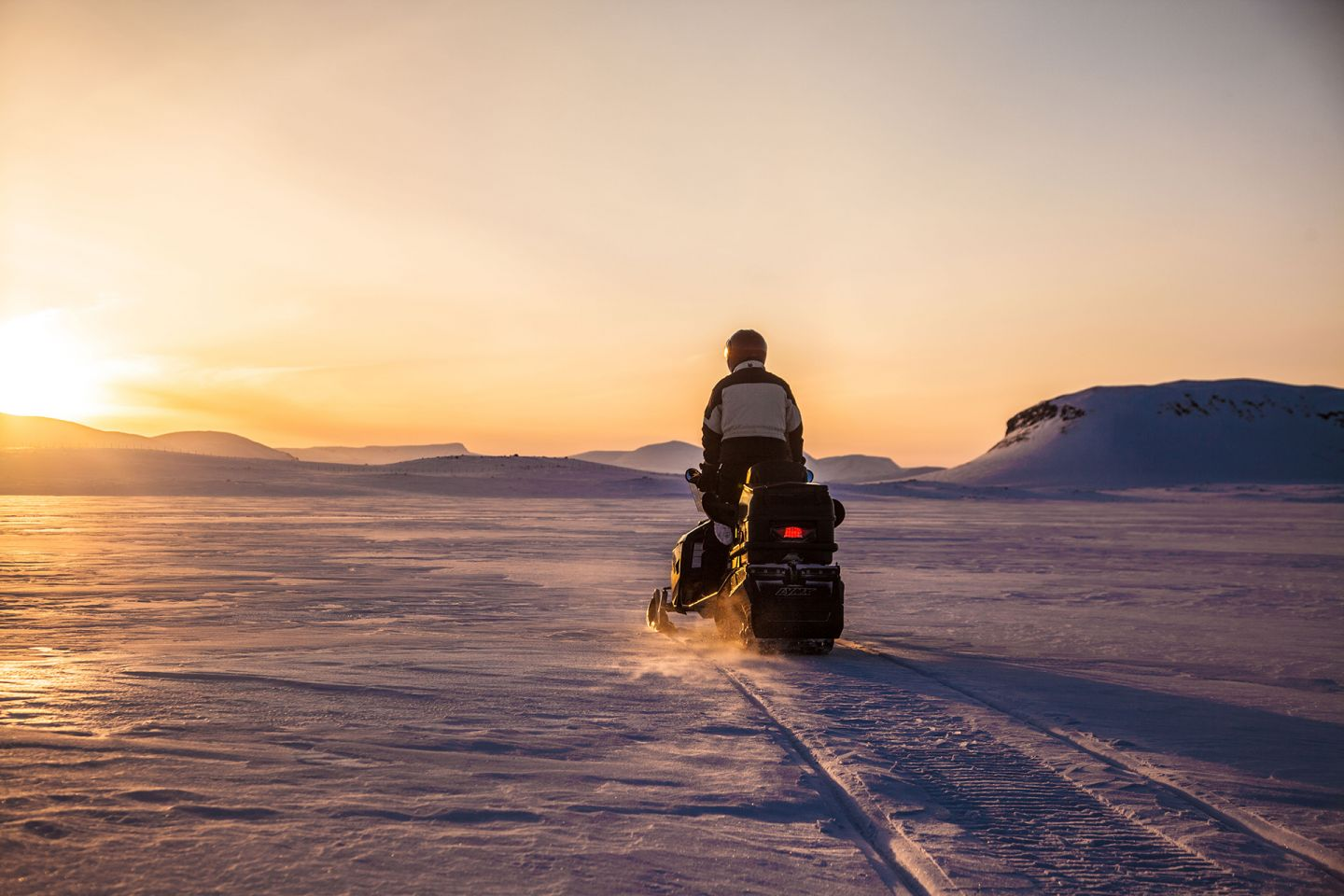 Snowmobile at sunset in the tundra