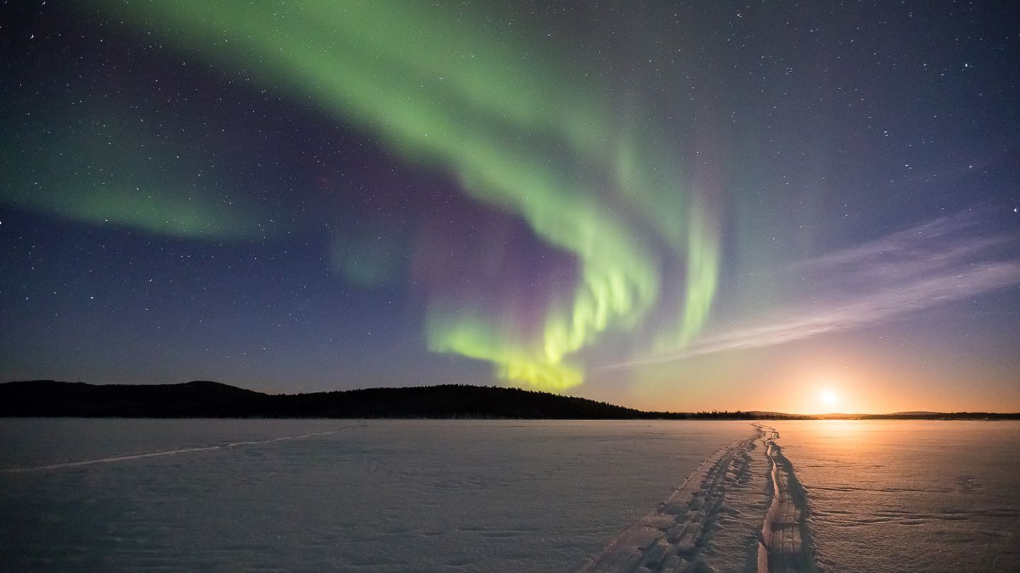 Snowmobile tracks on a frozen lake leading to the rising moon under the Aurora Borealis in northern Finnish Lapland