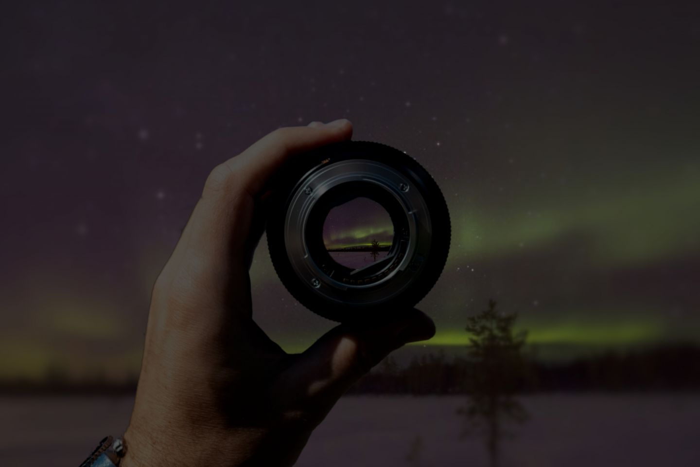 Close-up of northern lights in a camera lens in Finnish Lapland