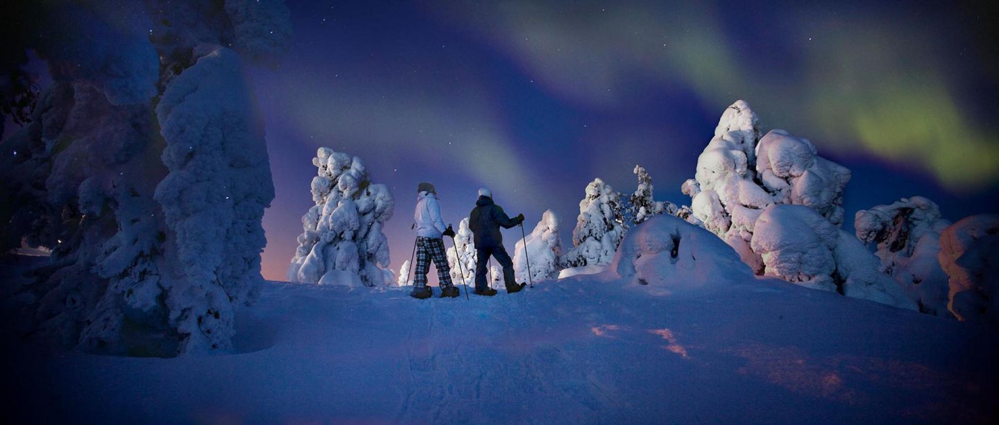 Snowshoe hike in winter under the Northern Lights