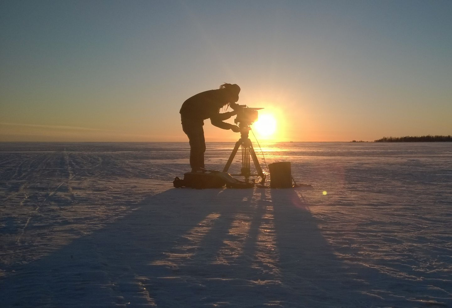 Filming on the snow against a sunrise