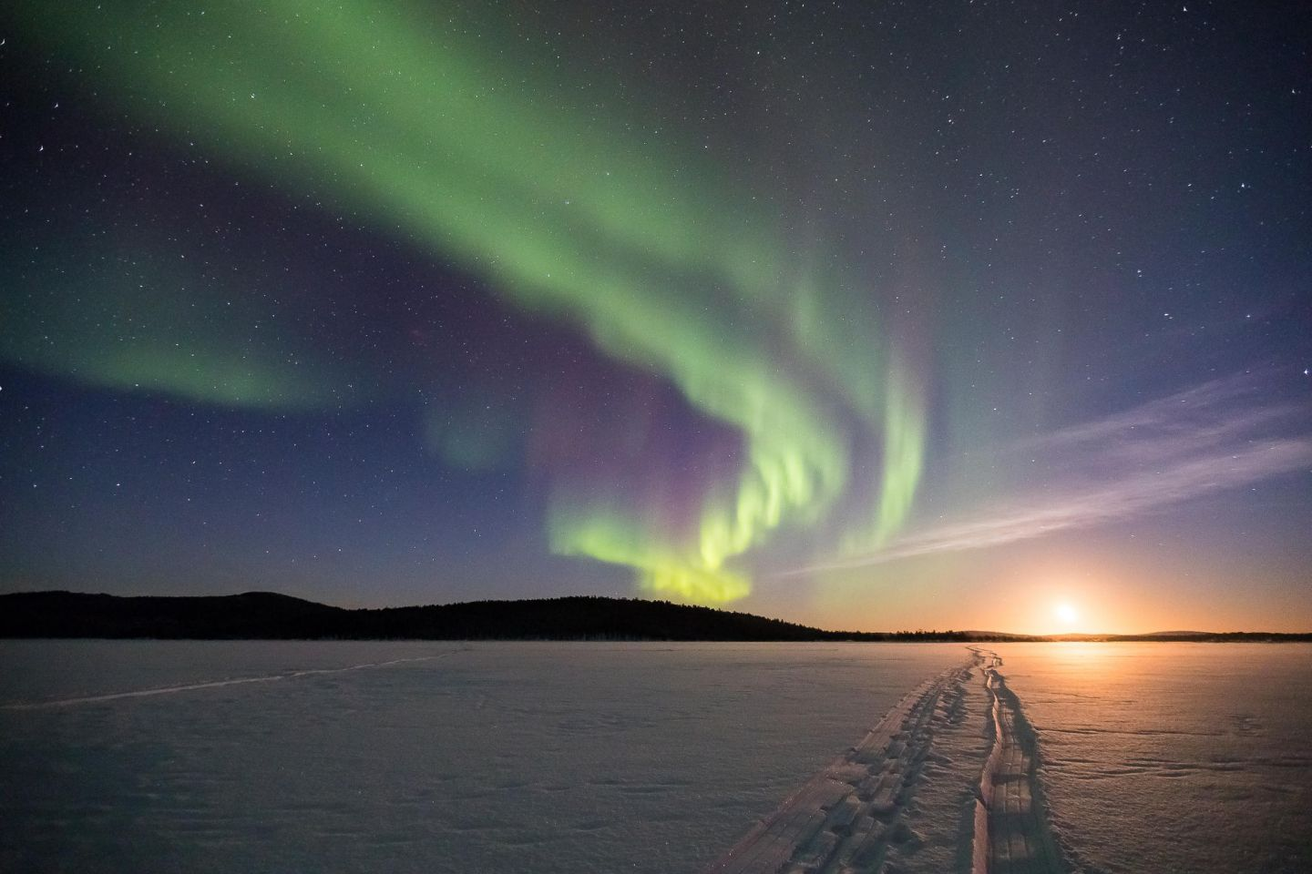 Path across snow under Northern Lights