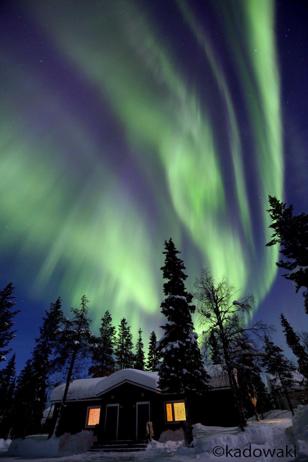 Auroras over a snowy cabin