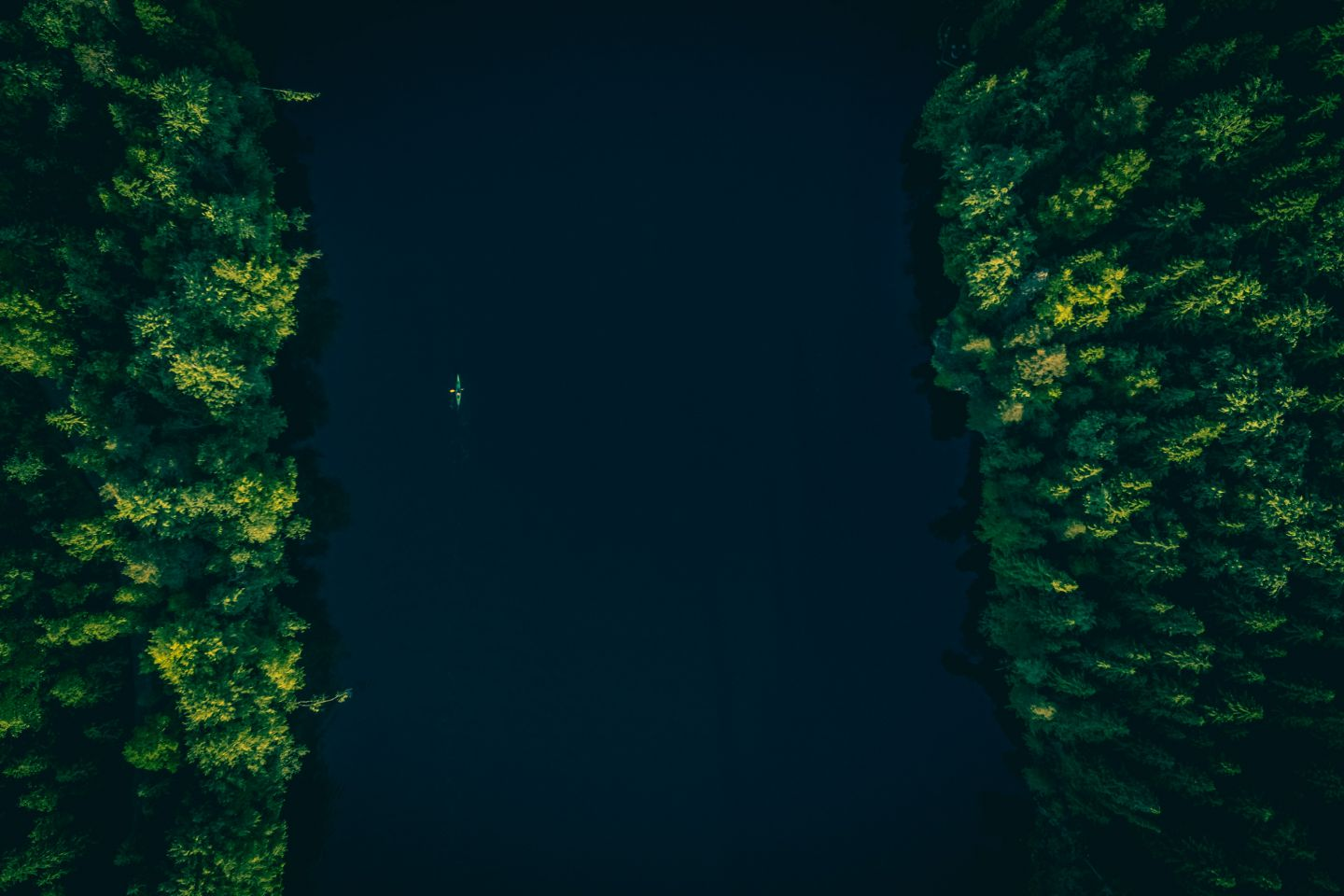 A canoe glides along a dark river in Finnish Lapland