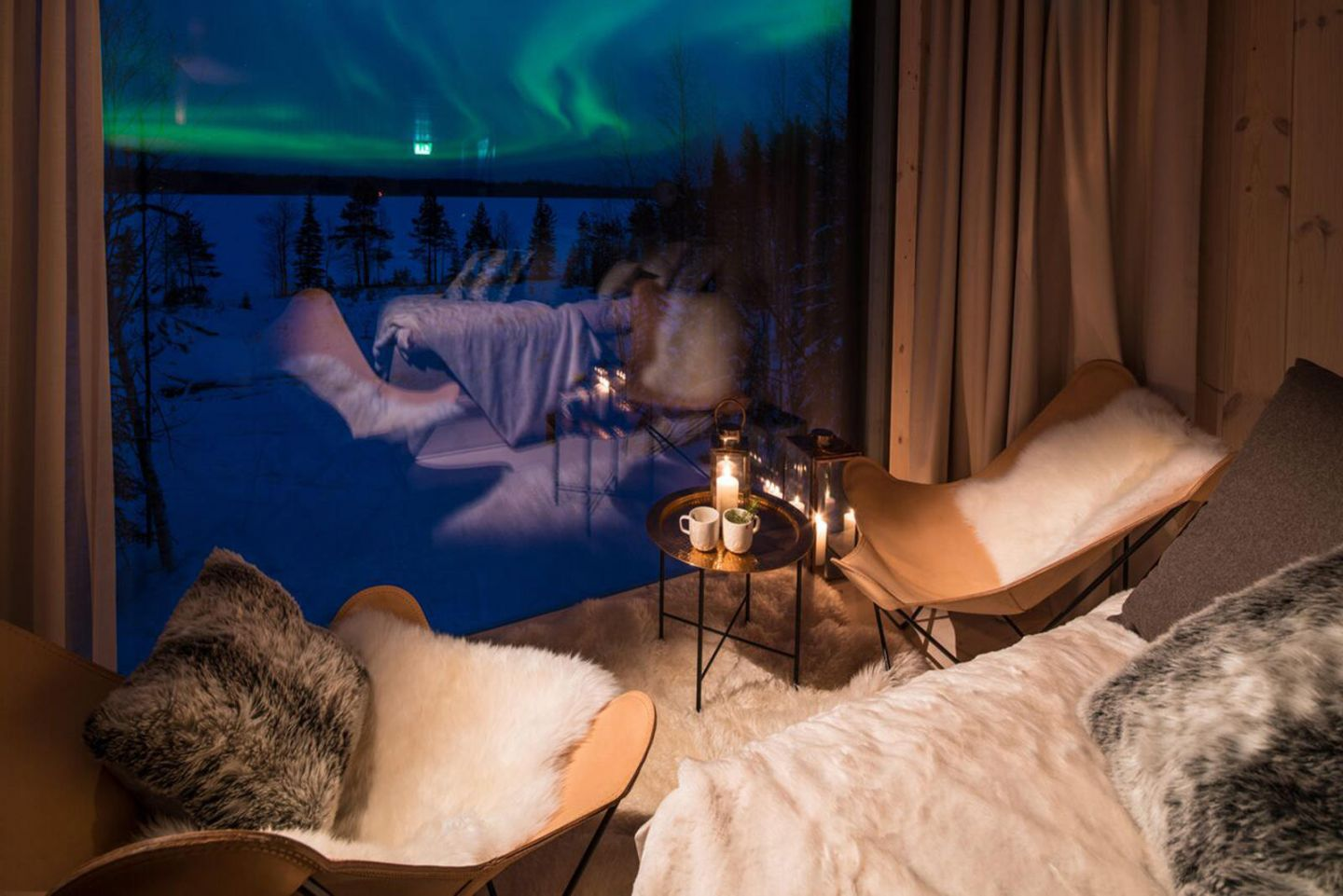 Northern Lights beyond the window at Arctic TreeHouse Hotel, a luxury hotel in Rovaniemi, Finland