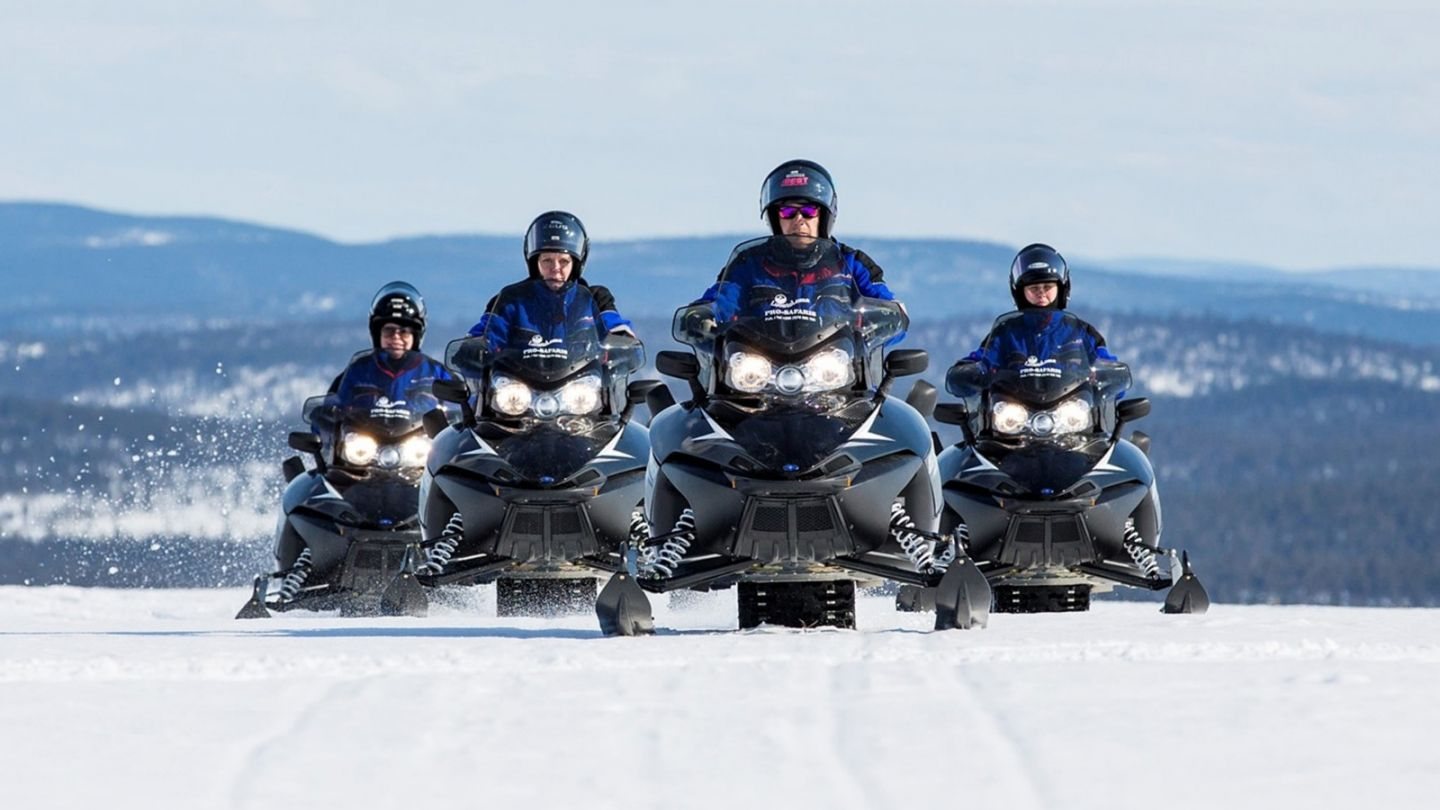 Snowmobiling across frozen Lake Inari in northern Finland in spring
