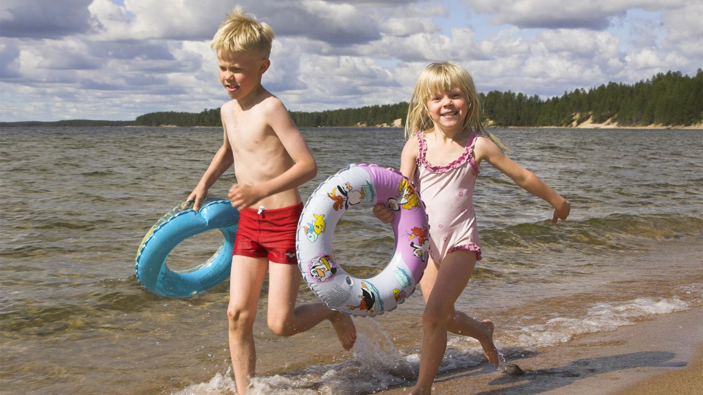 Children playing at the beach under the Lapland summer sun