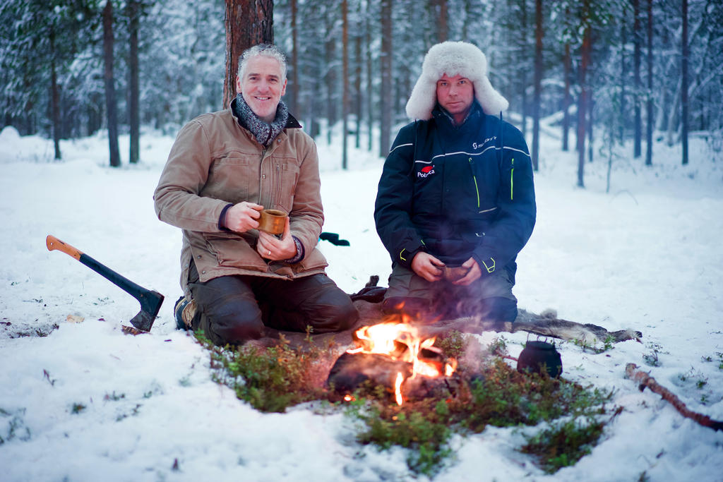 Gordon Buchanan enjoys the fire with a reindeer herder in Inari, Lapland