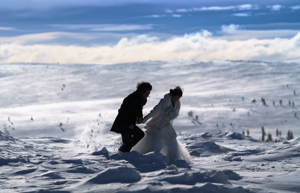 Wedding couple rushes across the deep snow in Lapland