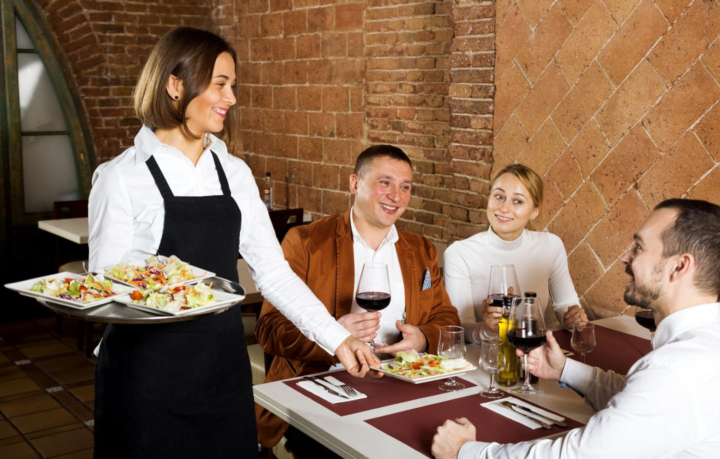 Happy female waiter carrying order for visitors in city restaurant