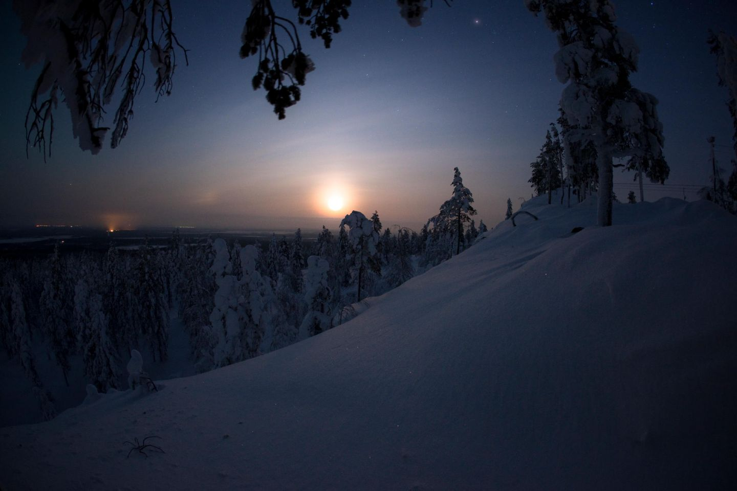 Sun rising over a dark snowy forest hill in the Arctic