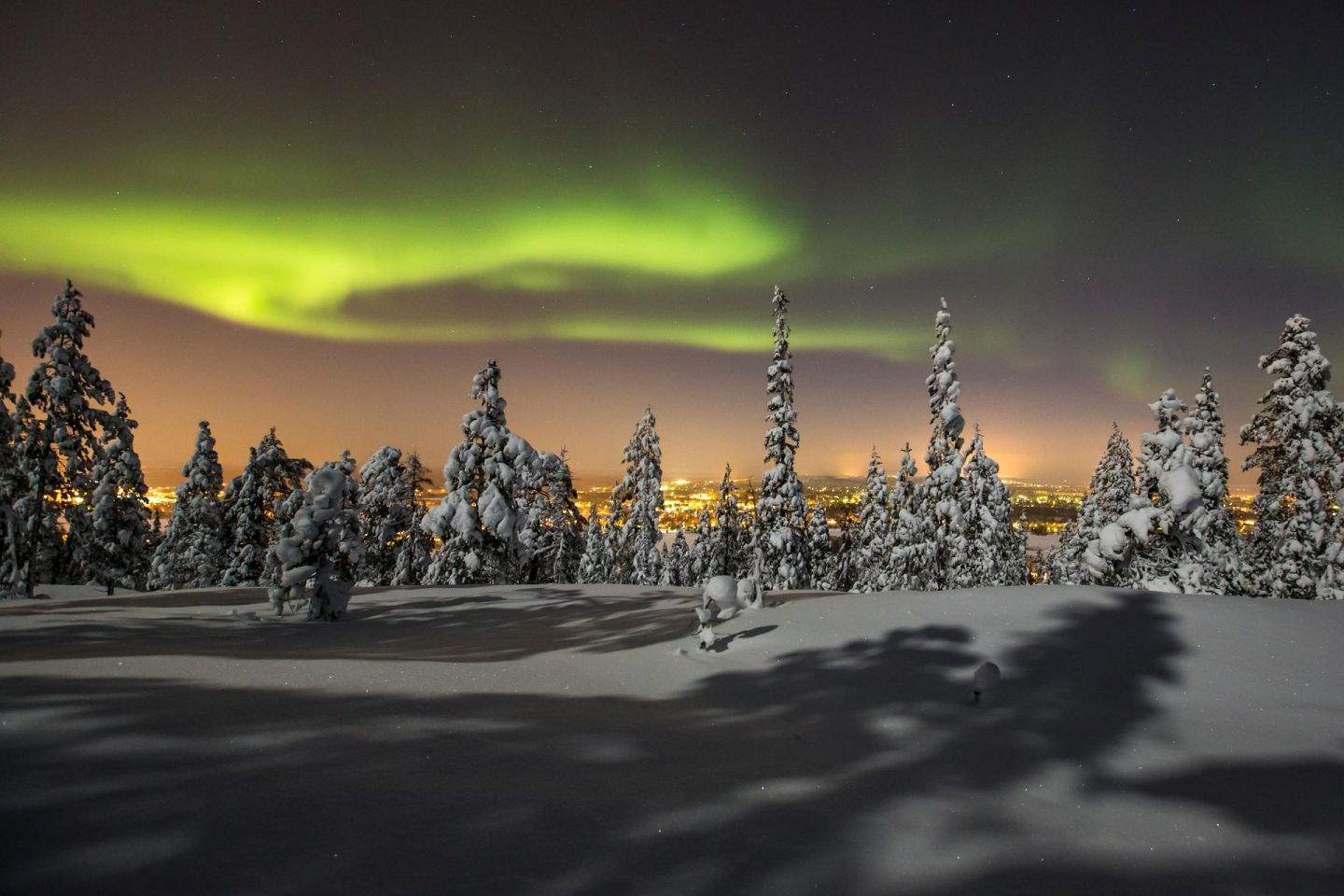 Northern Lights over the distant city of Rovaniemi in northern Finland