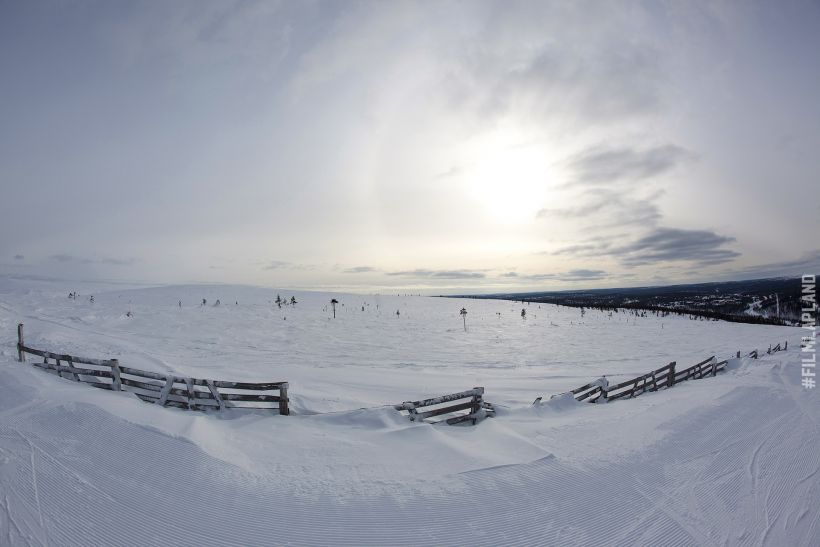 Sun shines behind the clouds over a vast snowy field in Inari, Finland