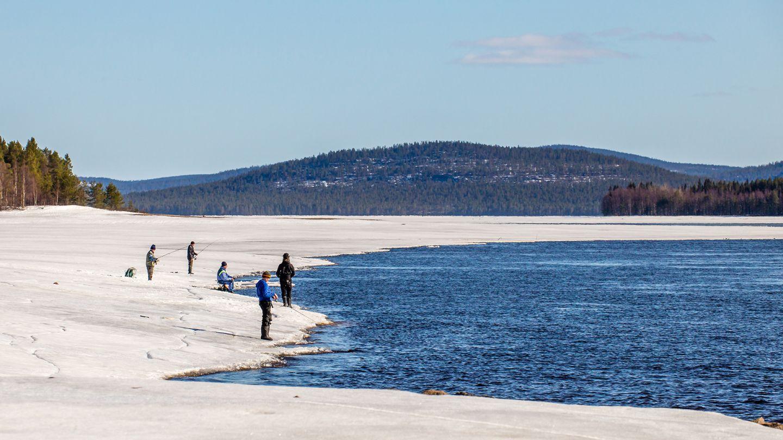 Fishing in a daylight by the frozen river in Kemijärvi, Lapland