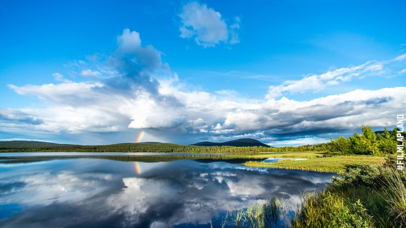 Rainbow reflected in an Arctic lake in Finland