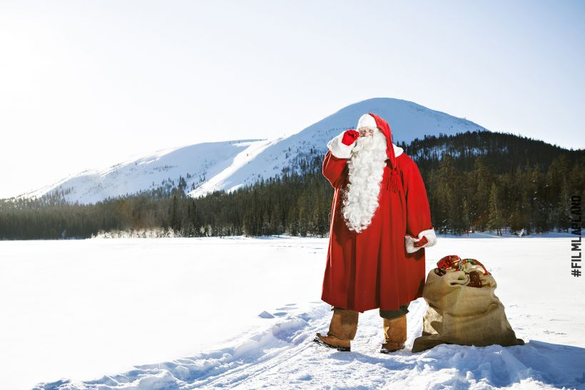Santa Claus stands atop a frozen lake in Lapland
