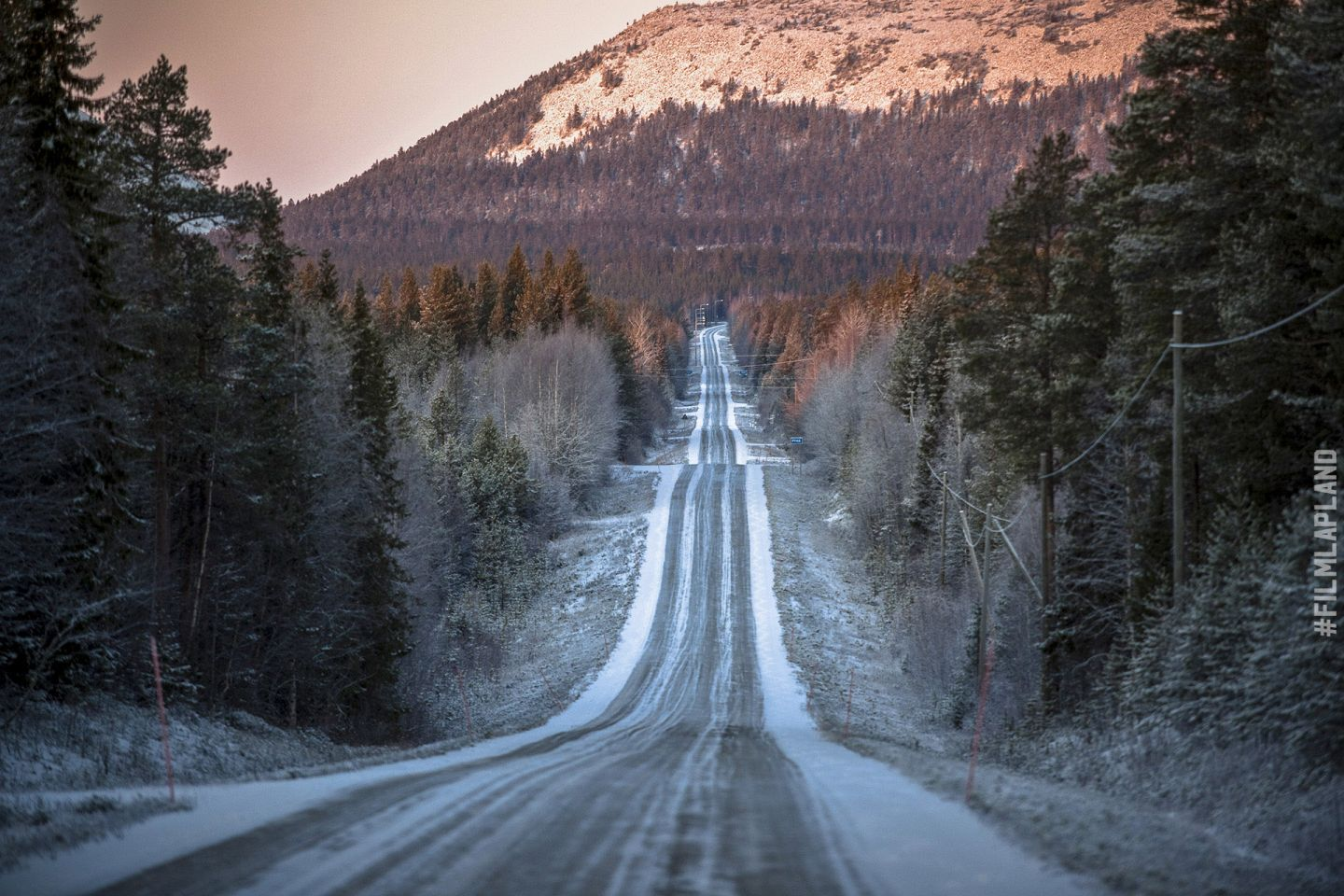Snow dusted highway through the Arctic hills in Pelkosenniemi, Finland