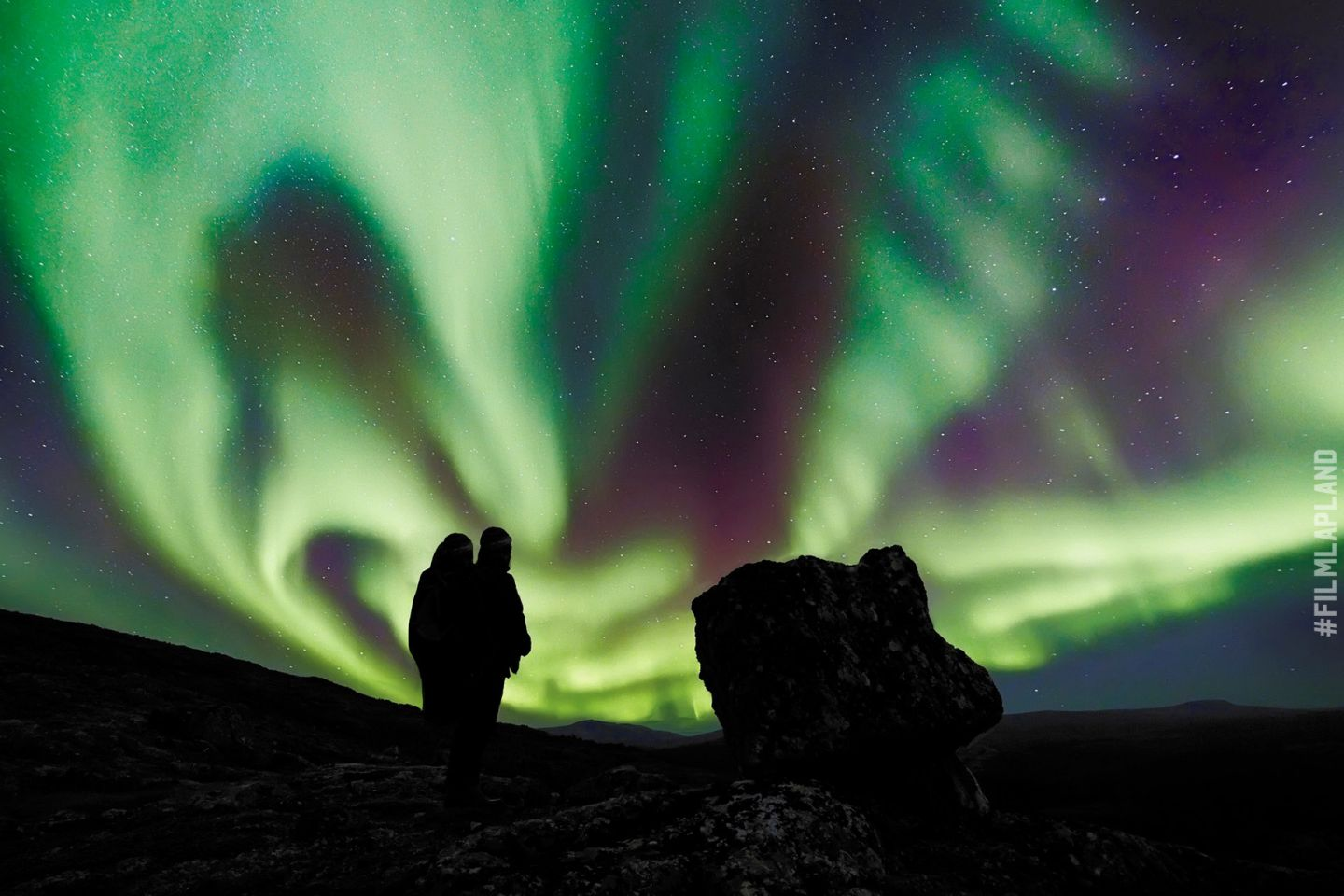 Northern Lights over spectactors in a Lapland field