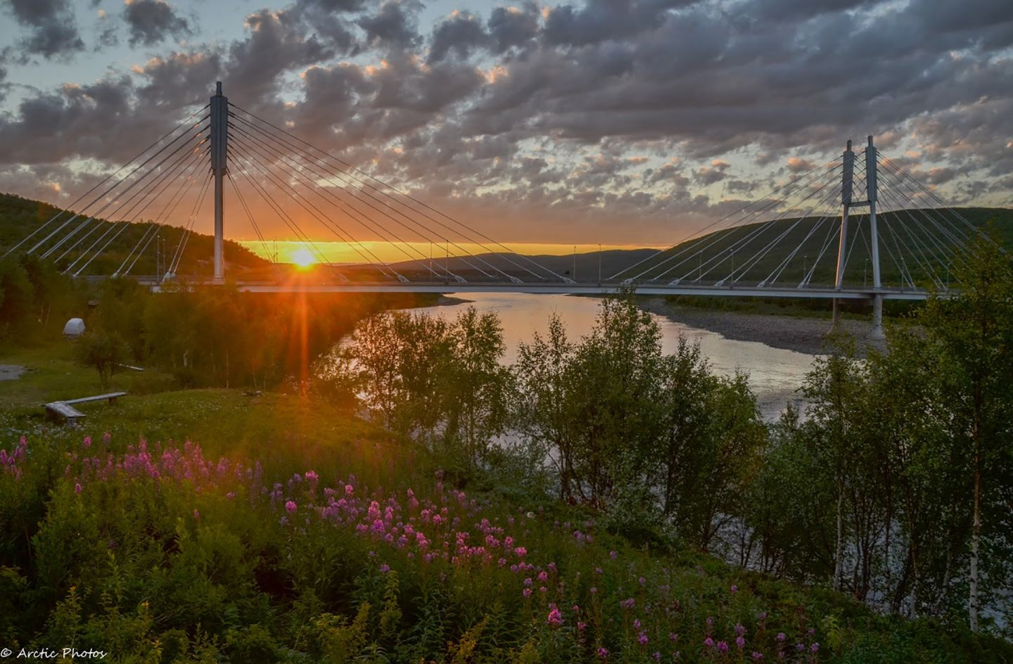 Sun sets in the horizon behind bridges in Utsjoki, Lapland