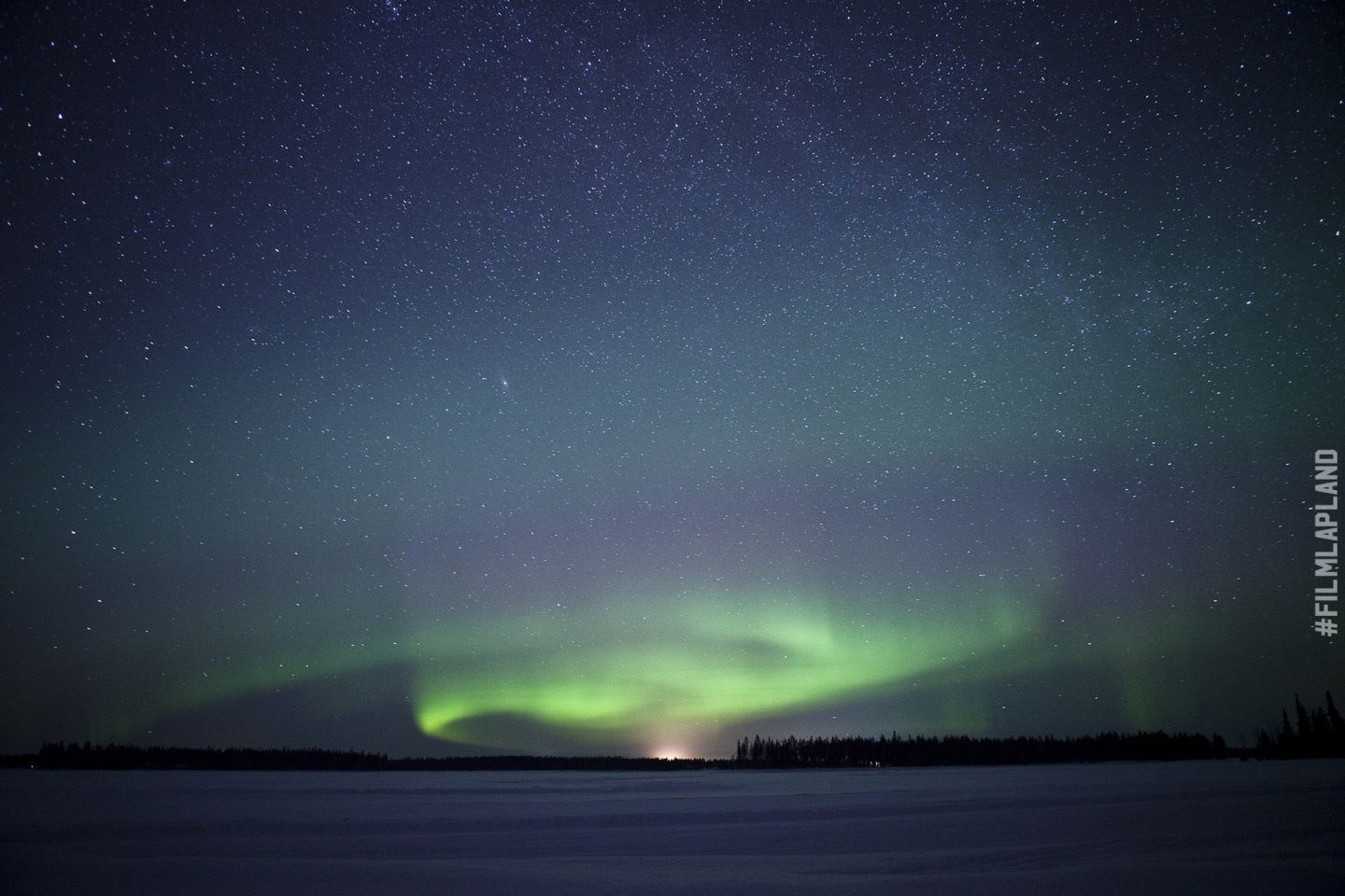 Northern Lights over snowy frozen lake in Sodankylä, Finland