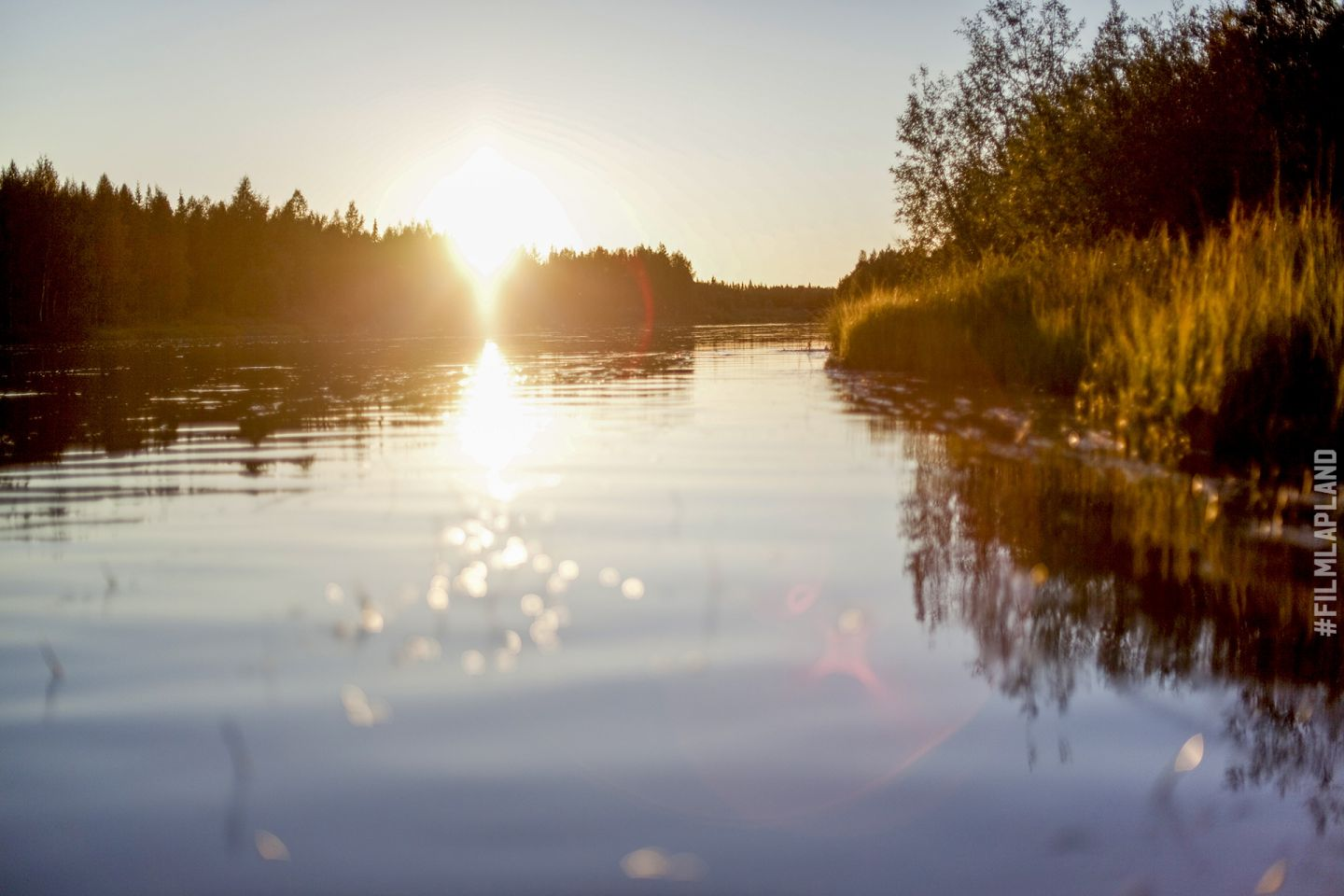 Sunset over a shimmering lake in Sodankylä, Finland