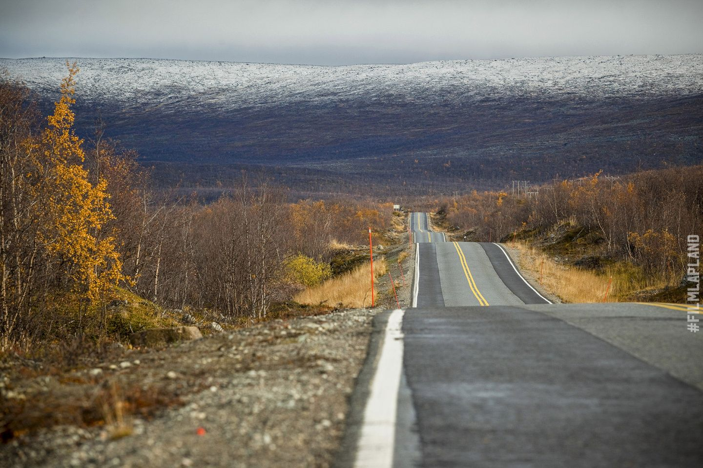 Rolling highway road in Kilpisjärvi, with Arctic hills in the distance