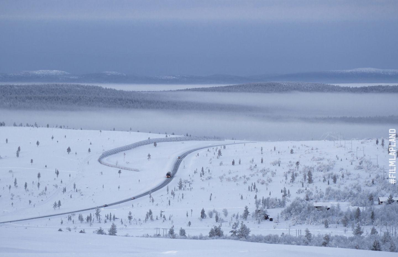 snowy road through gentle Arctic hills, in Inari, Finland