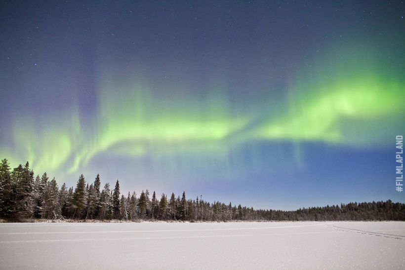 Northern Lights over trees and frozen lake in Rovaniemi, Finland