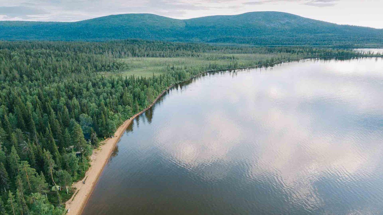 Red sand beach beside forest in Pallasjärvi, Finland
