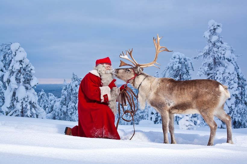 Santa claus kissing reindeer in Rovaniemi, Finland