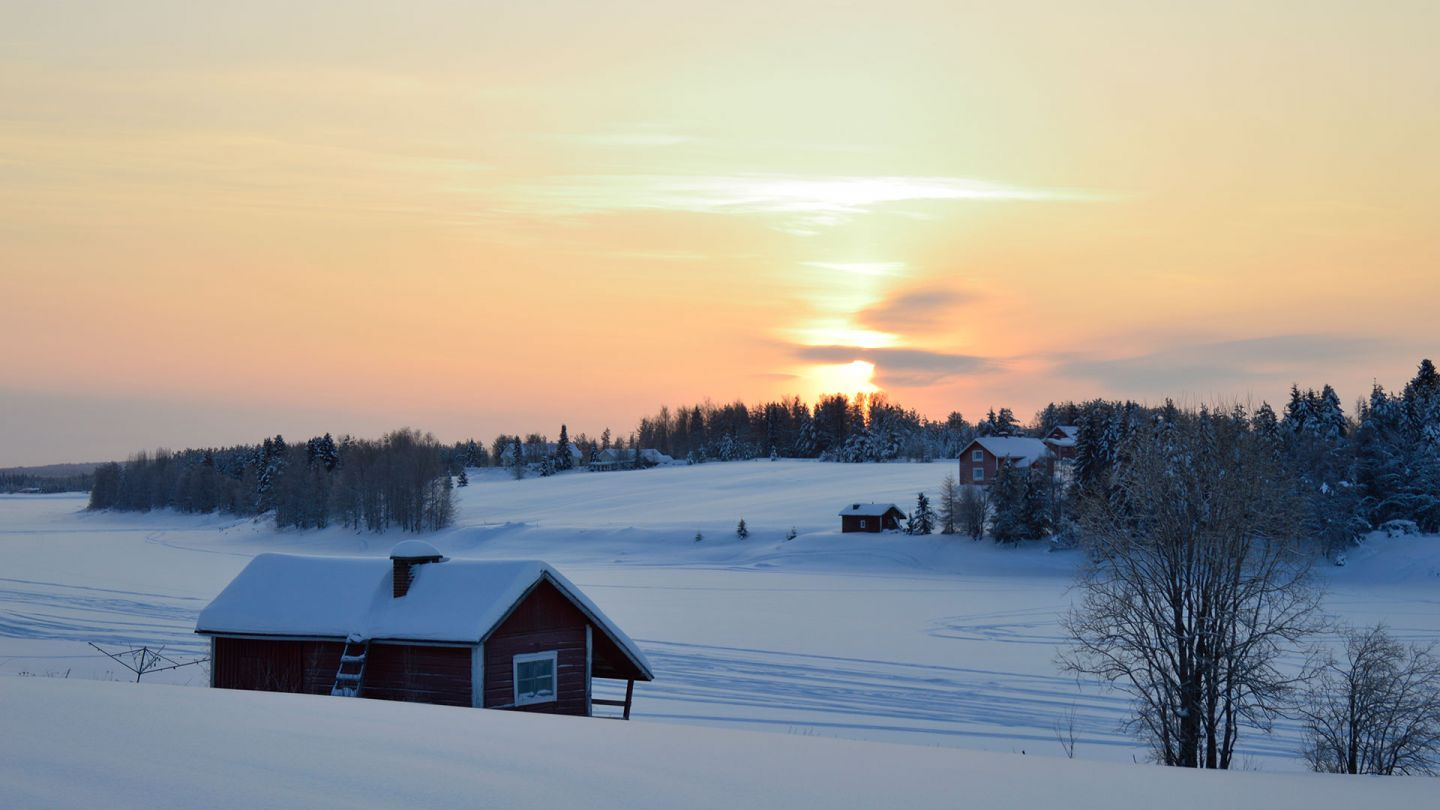 River bank and old village during winter with a sunset on background in Savukoski, Finnish Lapland.