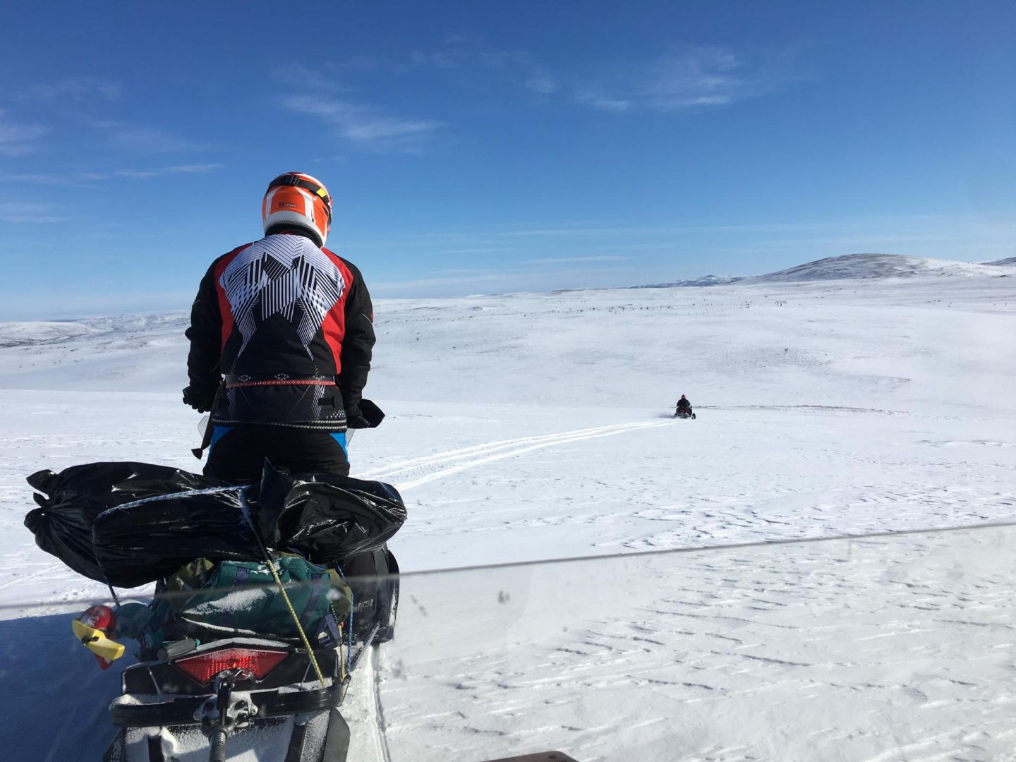 A snowmobile flies across an Arctic fell in Lapland, Finland