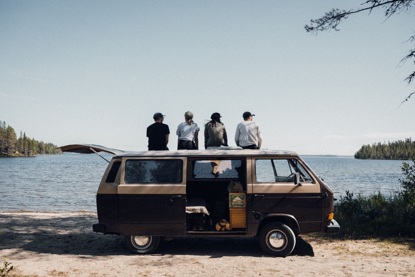 Group of Instagram Influencers sitting on top of the van staring at the lake ion Finnish Lapland