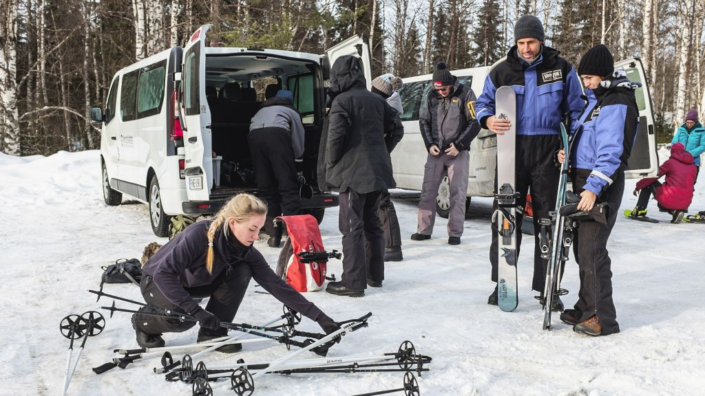 Female guide preparing skis with guests in lapland winter