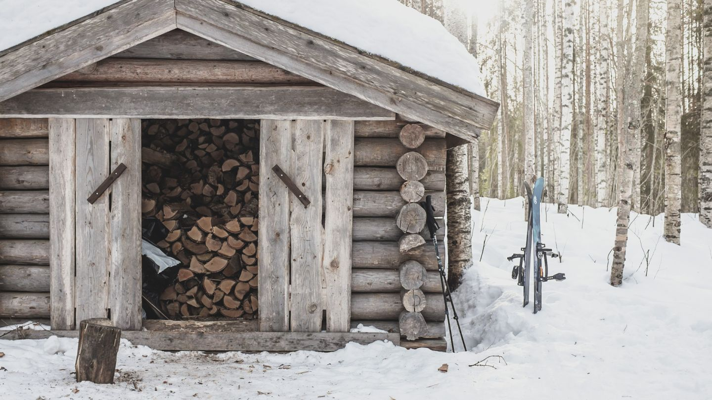wood shed in winter with skis