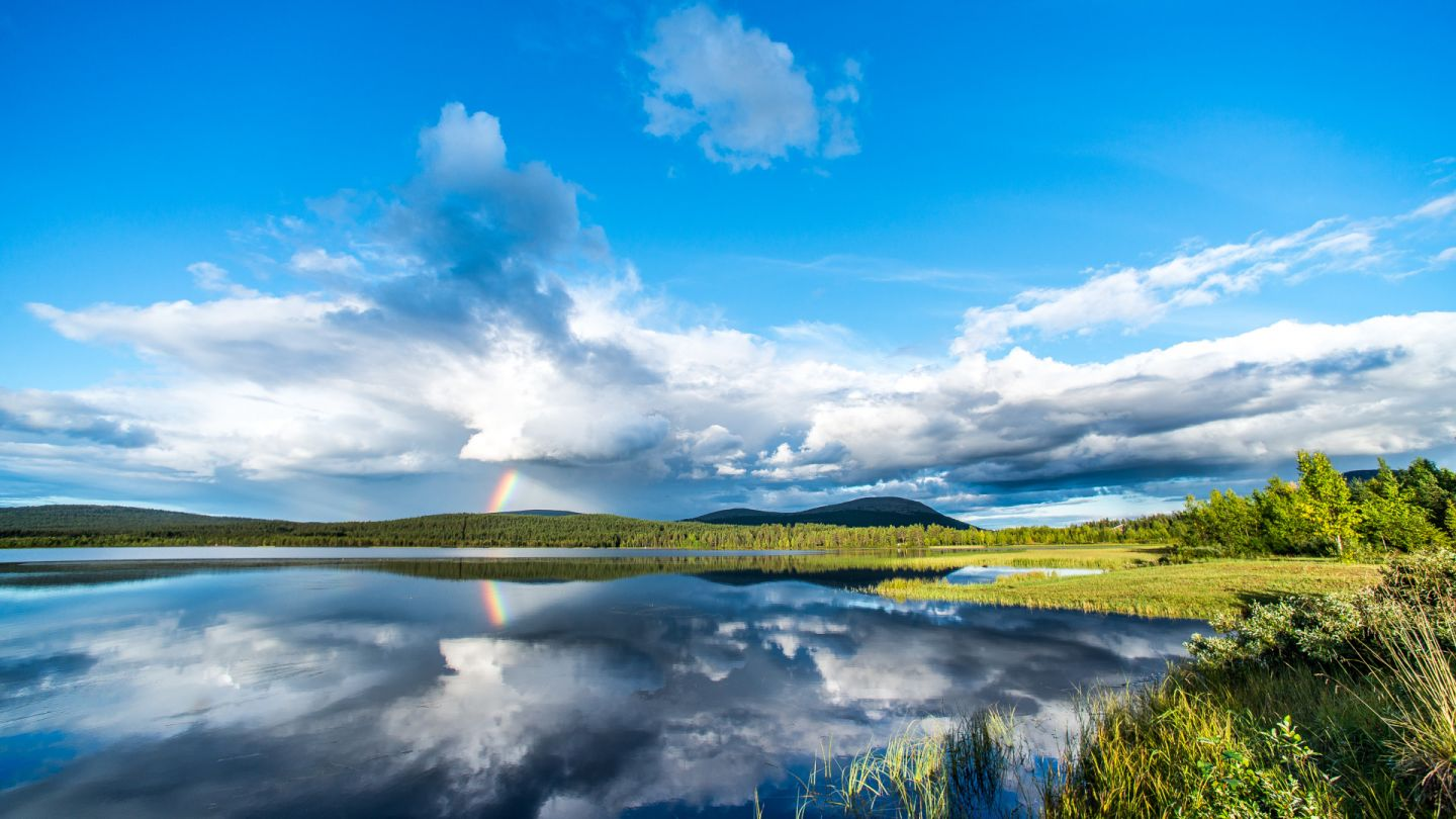 A rainbow during a sunny day by a lake in Finnish Lapland