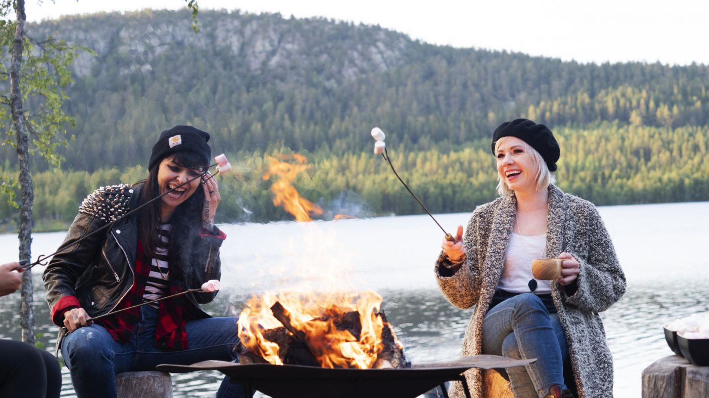 Carly Rae Jepsen and her crew enjoying marshmallows by a campfire in Finnish Lapland
