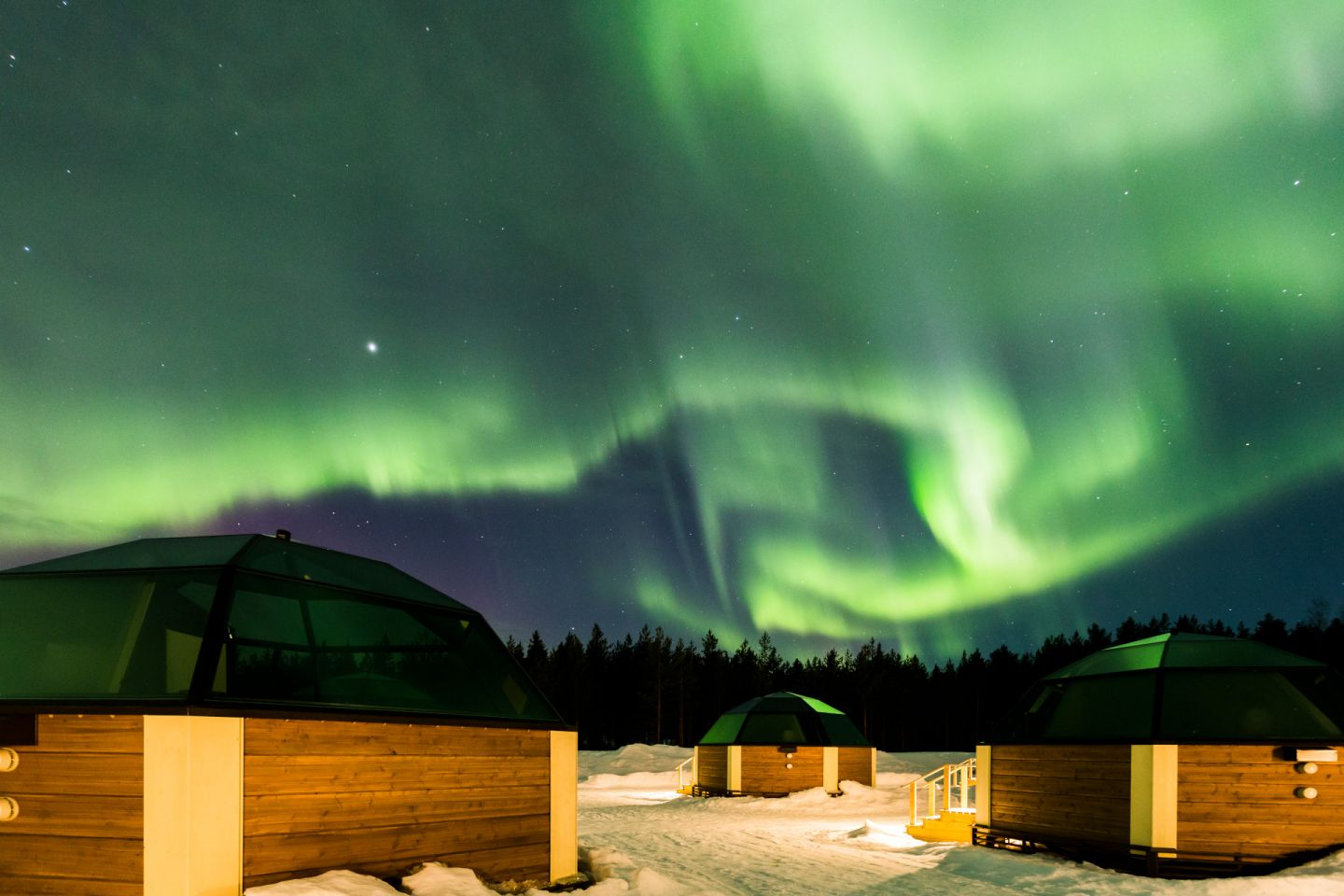 Auroras over glass igloos in Finnish Lapland