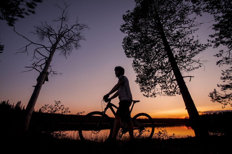 Biking at sunset in the Arctic wilderness of Savukoski, Finland