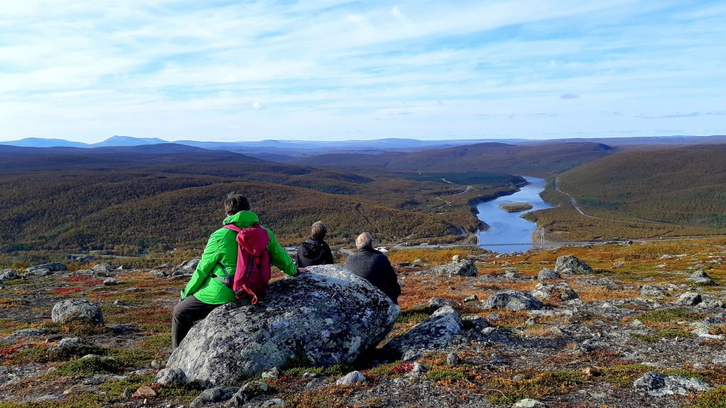 Travellers sit on a rock and watch a beautiful autumn River Tenojoki scenery in Utsjoki