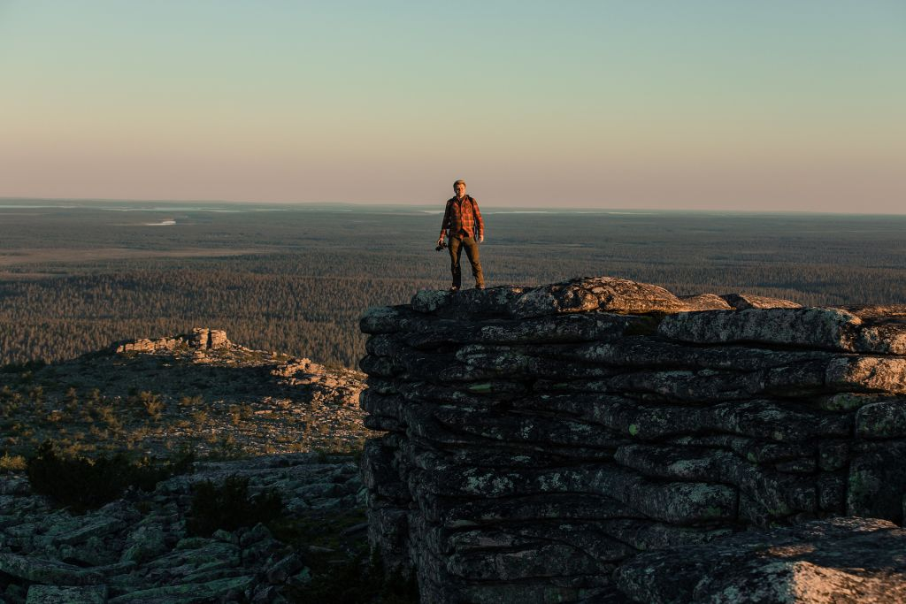 Photographer standing atop of fell