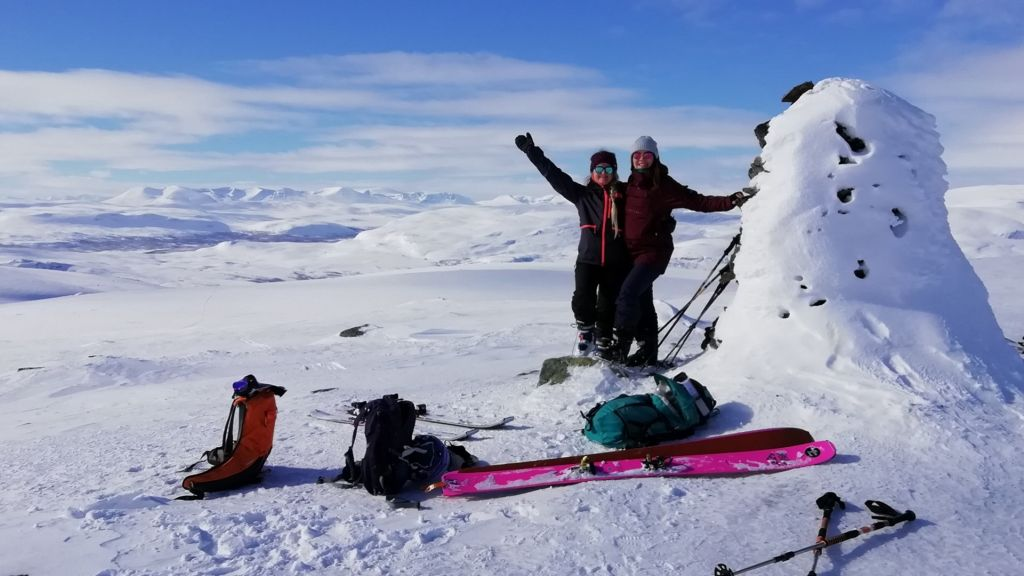 Two people with ski gears on top of a fell in Enontekiö in the middle of snowy winter.