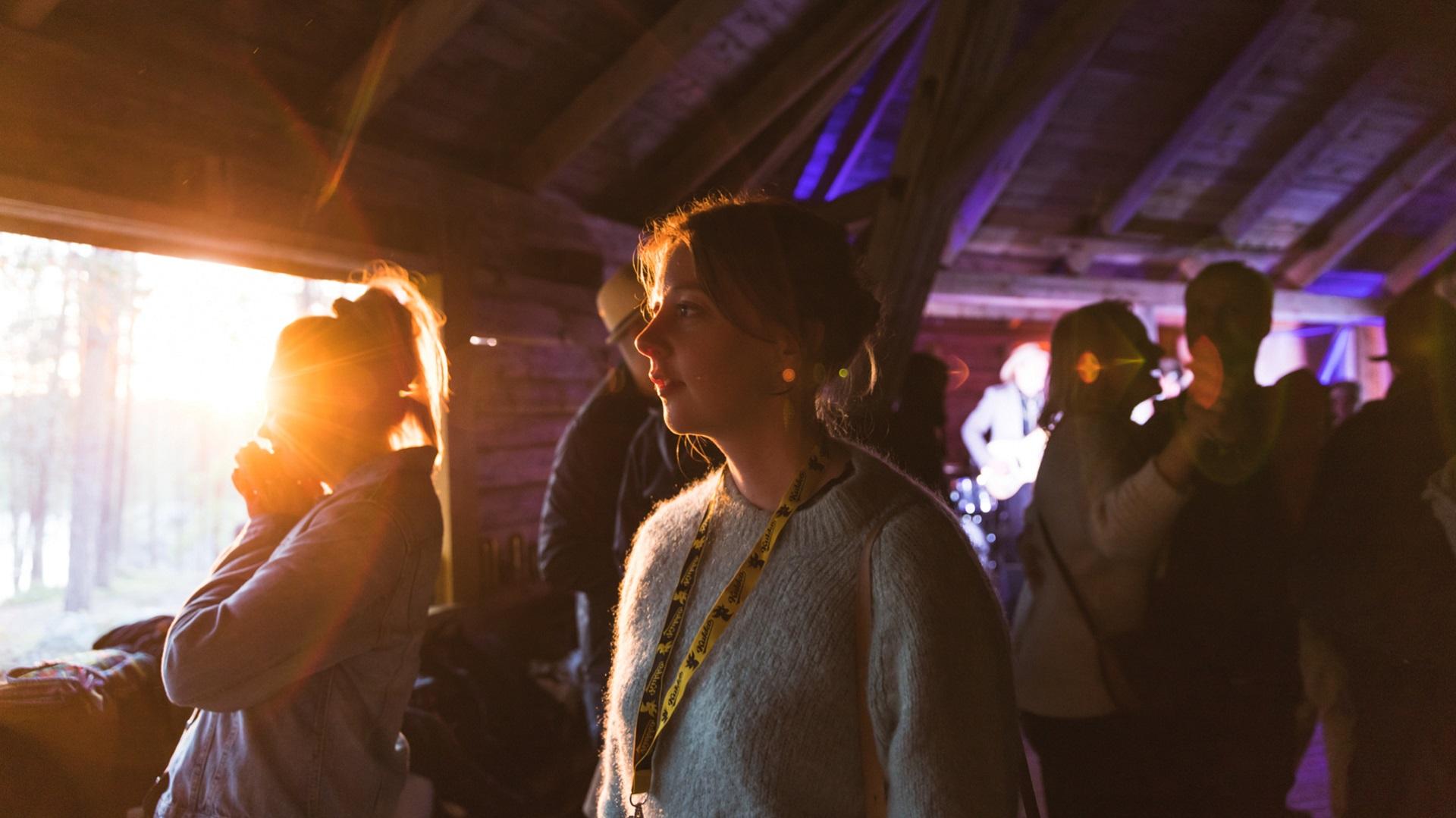 Nainen nauttii Sodankylän elokuvafestivaaleista ihmisten ympäröimänä ja tunnelmallinen valo paistaa rakennukseen sisälle.