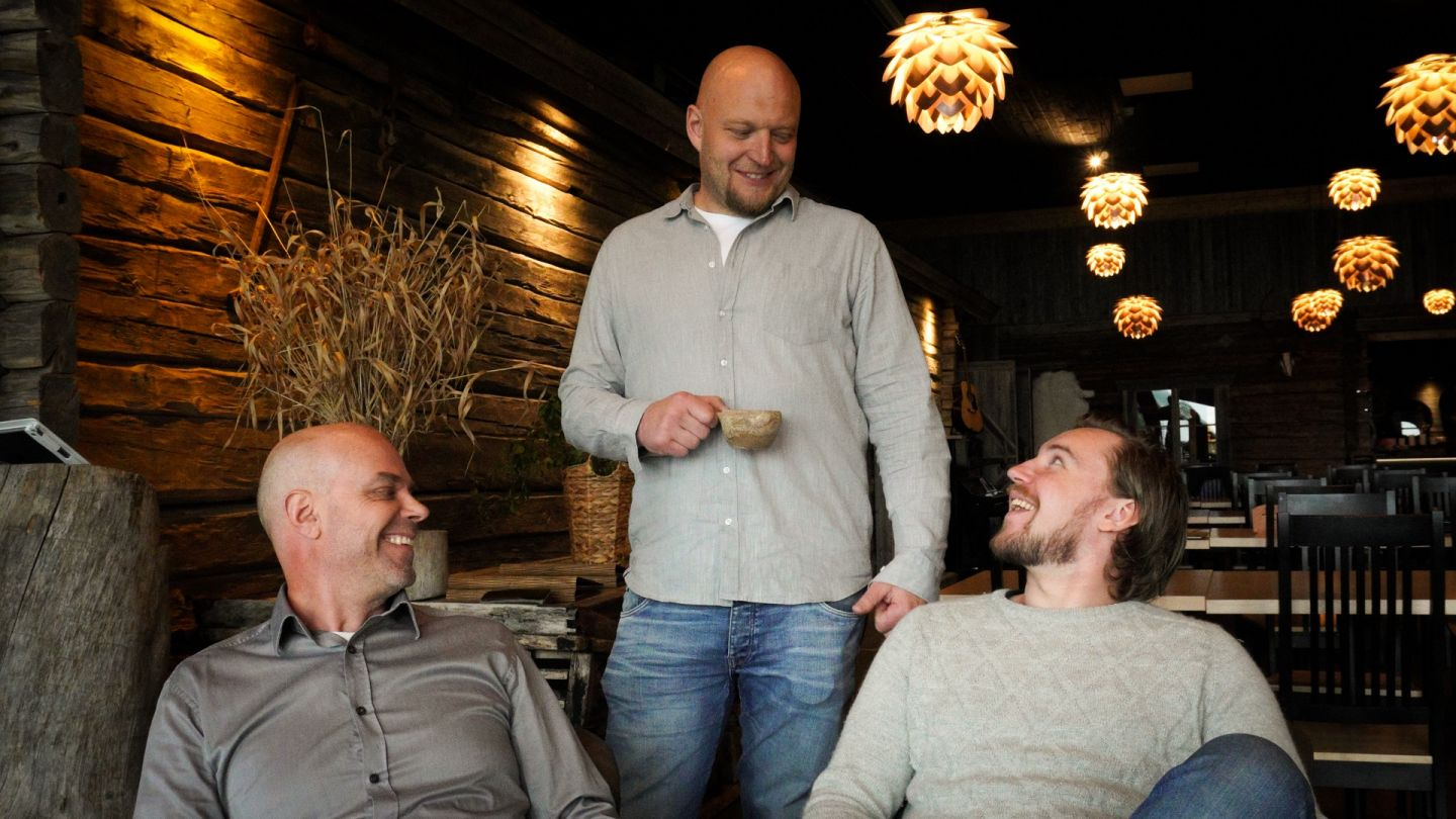 The three owners of Apukka Resort are having coffee and a conversation in the dining area of the hotel in Rovaniemi, Lapland.