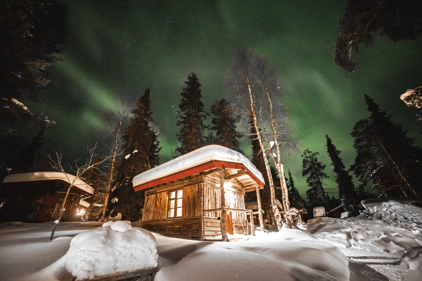 Northern Lights over a log cabin at Tankavaara Gold Village, a special winter accommodation in Sompio, Finland